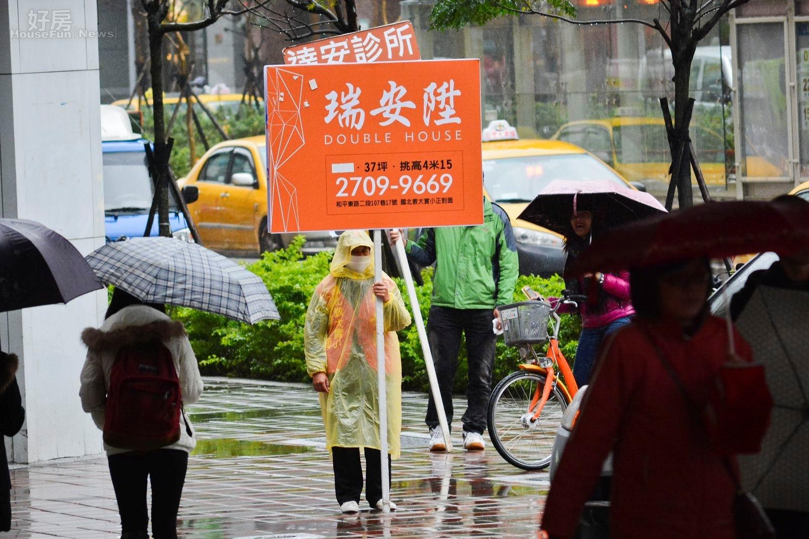 即使下雨天,在人潮眾多的地方,也時常看見舉牌工人穿著雨衣站在交通要道 宣傳建案廣告。(好房News記者 陳韋帆/攝影)