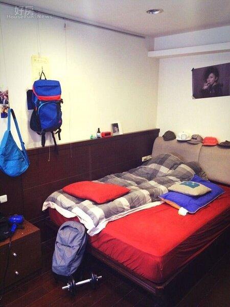 9.臥房牆上貼著偶像孫燕姿的海報,床組則是咖啡色系搭配紅色床罩。