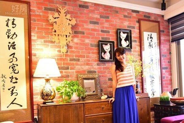 3.客廳沙發旁整面紅磚牆即為「爺爺奶奶牆」,上面掛有兩幅字畫與貓咪刺繡即出自於爺爺之手。