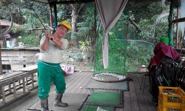 5.吳富德在農園廣場簡易高爾夫練習區自娛。