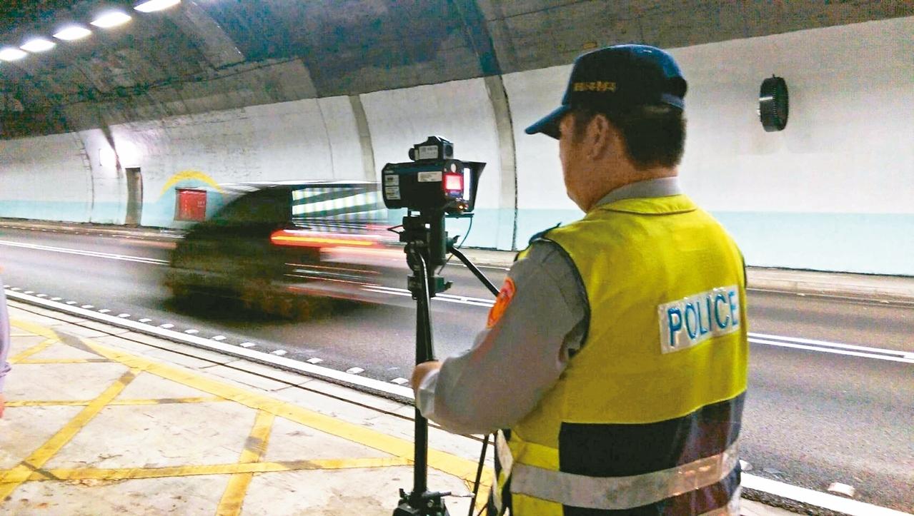 國道警第九大隊員警,昨天起在雪隧內取締龜速車,必須忍受隧道內高溫及吸入廢氣,非常辛苦。(記者戴永華/攝影)