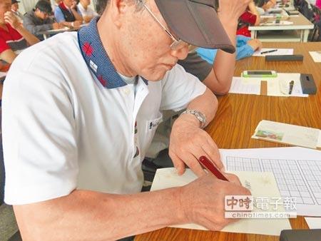 嘉義郵局15日舉辦書寫比賽,68歲周銘懷全神貫注寫字。(高錦如攝)
