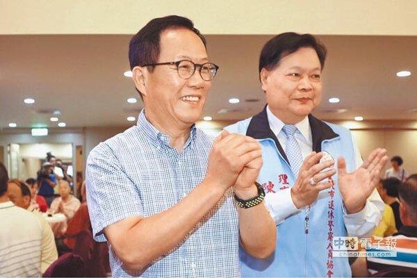 國民黨台北市長參選人丁守中(左)出席國軍英雄館的「台北市退休警察人員協會慶生會」,拱手向與會人員致意。(中央社)