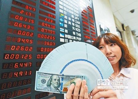 學者認為隨著美國聯準會如期升息,強勢美元格局持續,台灣央行可能在明年第1季升息。圖為行員手持美金現鈔。(本報資料照片)