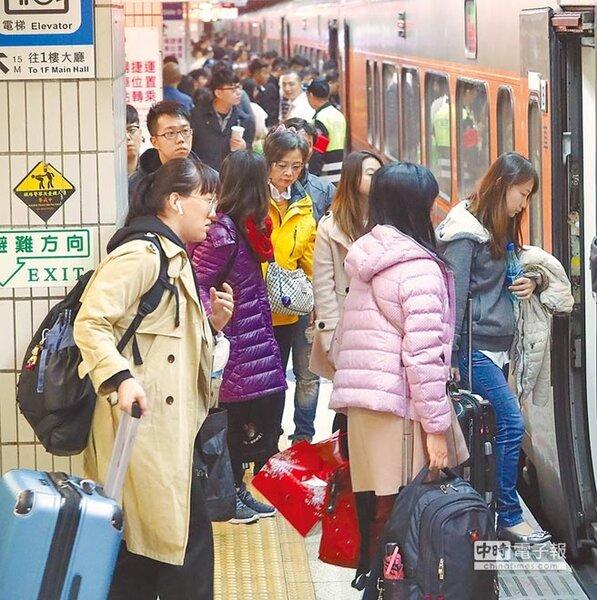 農曆春節連續假期的第一天,熙來攘往的車站出現返鄉過年人潮,在候車的月台旅客帶著行李,魚貫的進入火車。(季志翔攝)