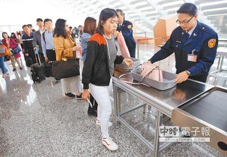 越南已被列為非洲豬瘟疫區,在桃園機場一航廈,搭乘越南航班的旅客排隊檢查手提行李。(范揚光攝)
