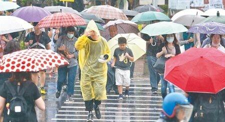 受到梅雨鋒面及西南氣流影響,中央氣象局對18縣市發出豪雨特報,提醒注意局部大雨或豪雨,台北市區一早就持續下雨,民眾準備雨具對抗雨勢。(劉宗龍攝)
