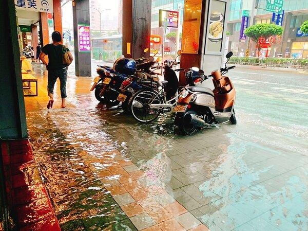 新北市三重雨灌道路,淹到連騎樓民眾都要拉褲管涉水前進。圖/臉書我們三重人 【241 Plus+】