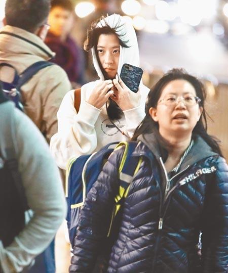 受到東北季風南下,北台灣26日傍晚氣溫驟降,不少外出民眾紛紛穿起外套及圍巾保暖。(劉宗龍攝)