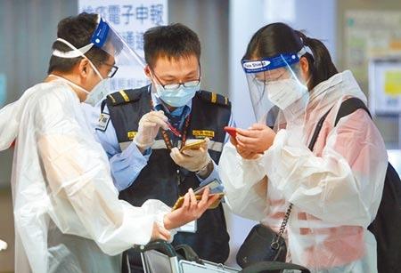 中央流行疫情指揮中心研擬開放「經濟泡泡」,放寬特定身分旅客入境檢疫條件。在桃園機場入境管制區內,防疫人員正協助2名身穿防護衣的旅客,上網填寫健康聲明書。(范揚光攝)