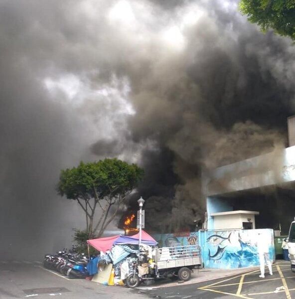 濱江市場8日上午停車場內部傳出火警,民眾直擊現場火勢延燒,黑煙猛烈竄出。圖/取自民眾臉書