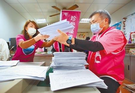 針對藻礁公投連署盛況不斷升高,在環團藻礁公投總部內,身穿粉色上衣的志工正忙著清點連署書。(范揚光攝)