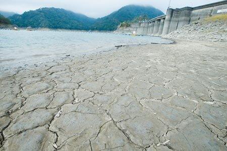 北部水情拉緊報,肩負灌溉重責的石門水庫,靠近大壩裸露的土地呈現龜裂狀。 (陳怡誠攝)