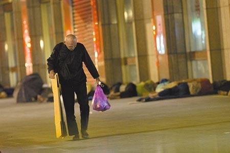 新冠肺炎本土疫情持續蔓延,繼北農、士林養護機構群聚感染後,台北車站亦傳出8名街友確診,台北車站23日深夜仍能看見大批街友睡在周邊。圖/杜宜諳攝