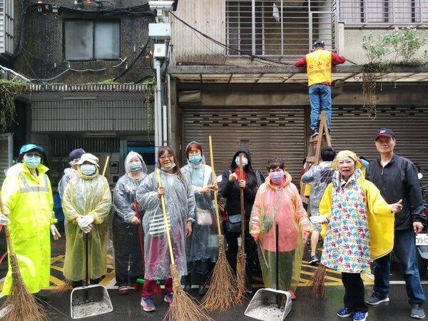 為了里內的環境衛生,下著大雨志工團隊,還是穿著雨衣,打掃防火巷弄!圖/里長提供