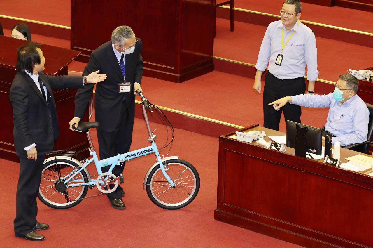議員王世堅(左)抨擊台北市長柯文哲(右)「假推廣腳踏車之名,行銷柯文哲之實」,並送給柯一輛刻有「政治不難,找回網軍而已」嘲諷意味的腳踏車。記者曾學仁/攝影