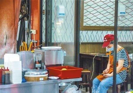 疫情警戒已降為二級,餐飲仍規定必須外帶的雙北及宜蘭,有機會在下周開放內用。圖為小吃店業者遲遲等不到客人上門,只好坐在一旁滑手機。(羅永銘攝)