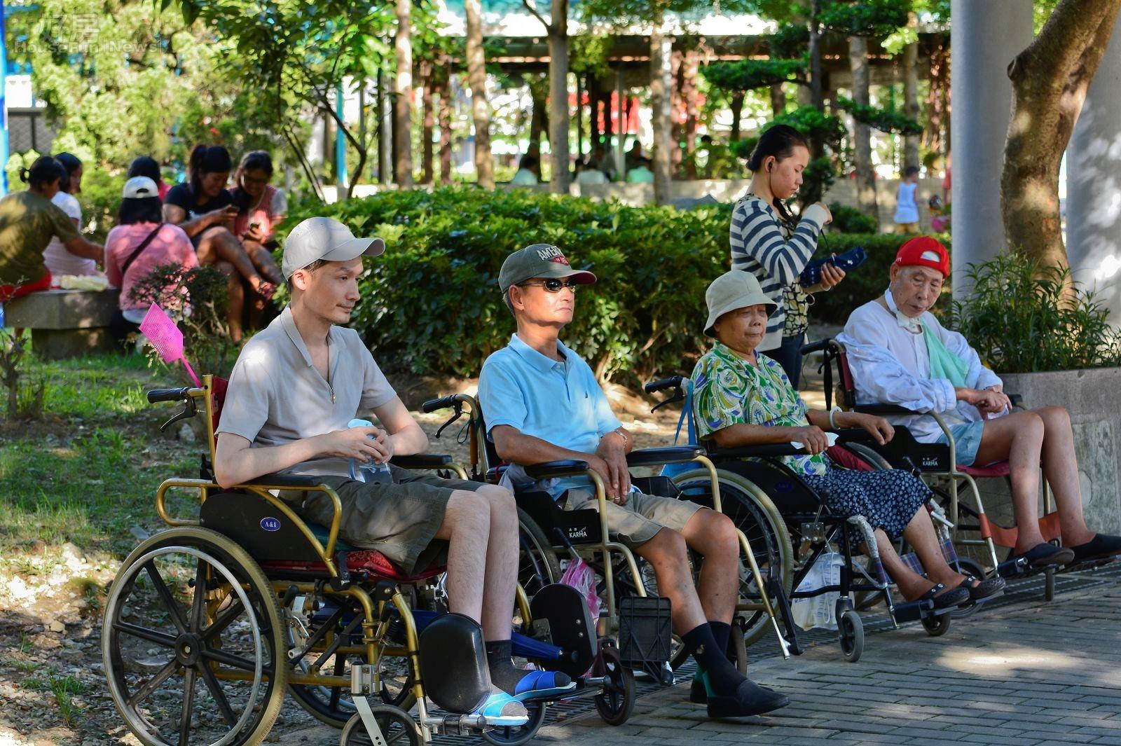 新北市中和區秀山公園,傍晚時外傭們將輪椅上的民眾一字排開,讓他們自己聊天,外傭們則聚集至後方聚會,僅剩一位盡責的看護仍陪著老人。(好房News記者 陳韋帆/攝影)
