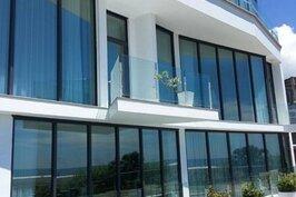 民宿外觀是白色有著大片落地窗的建築。