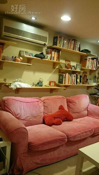 3.客廳擺放桃紅色沙發,後方層板上有書籍與她到各地採訪買回來的紀念品。